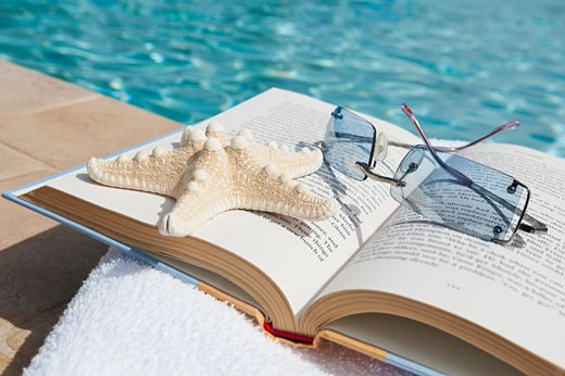 Book and sunglasses by swimming pool : Stock Photo