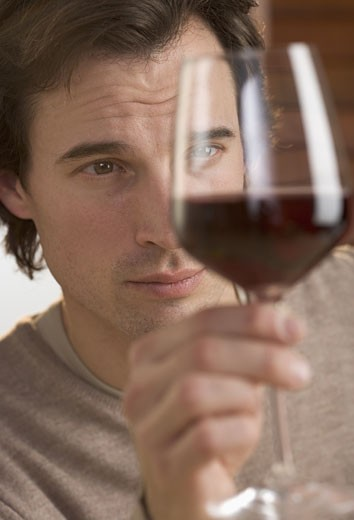 Closeup of man scrutinizing red wine : Stock Photo