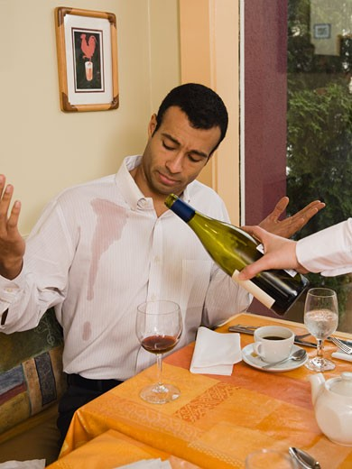Waiter spilling wine on customer : Stock Photo