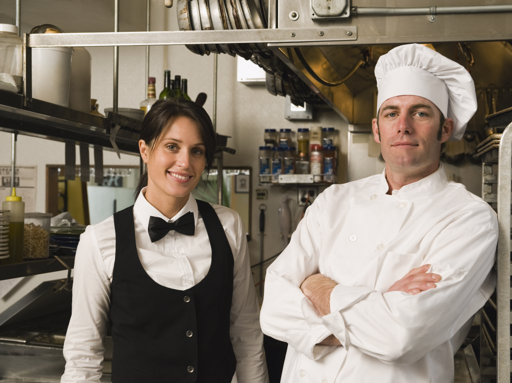 Stock Photo: 1795R-20501 Chef and waitress posing in restaurant kitchen