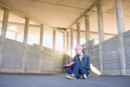 Young woman reading in urban setting : Stock Photo