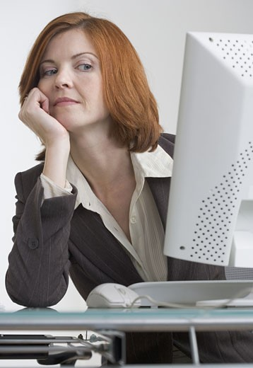 Businesswoman looking askance at her computer : Stock Photo