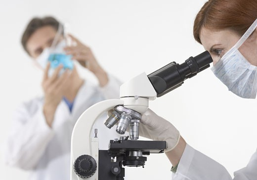 Scientists in laboratory with microscope : Stock Photo