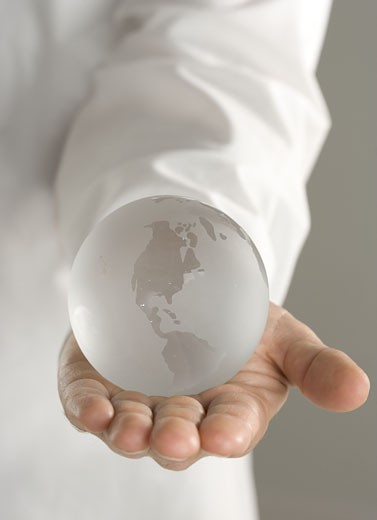 Glass globe held in outstretched hand : Stock Photo