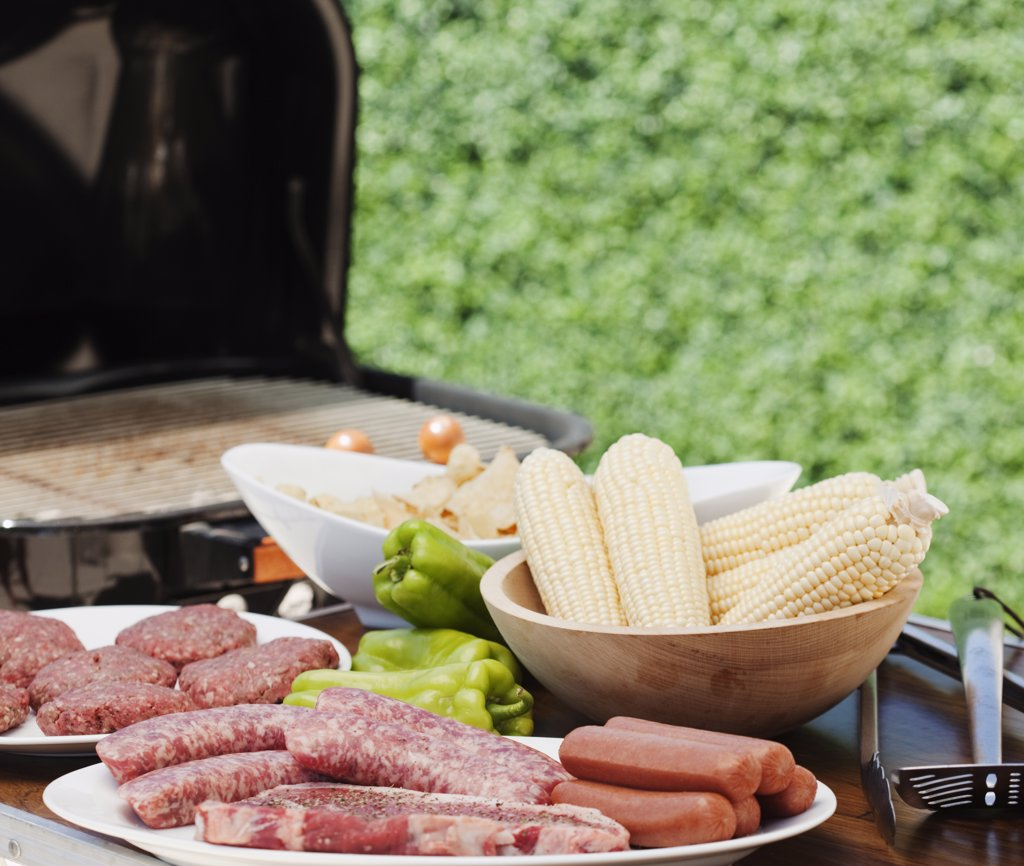 Corn and meats by a barbeque : Stock Photo