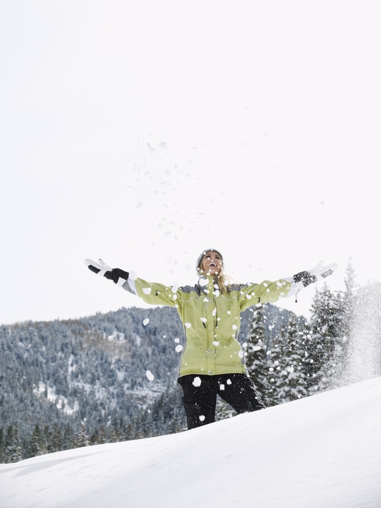 A woman throwing snow up in air : Stock Photo