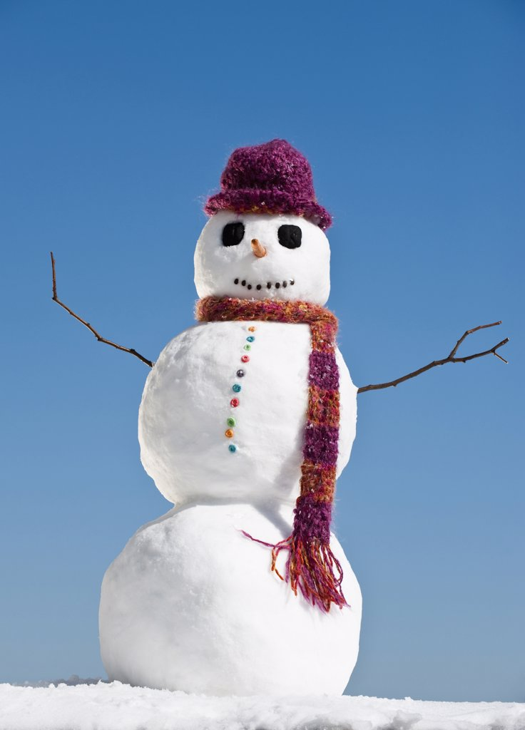 Snowman wearing hat and scarf, clear sky in background : Stock Photo