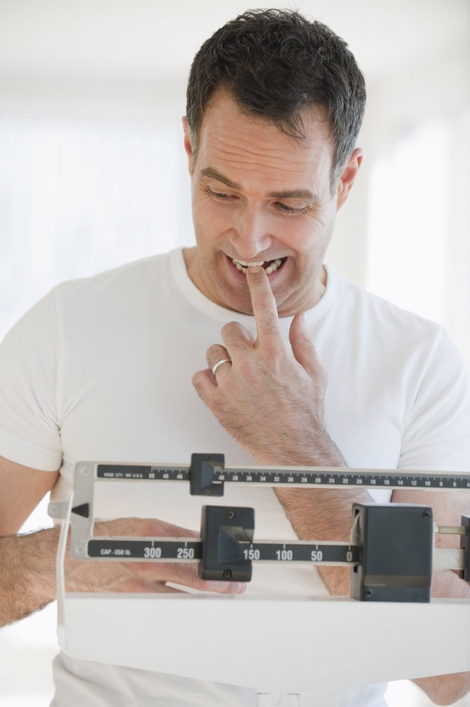 Mature man on scales : Stock Photo