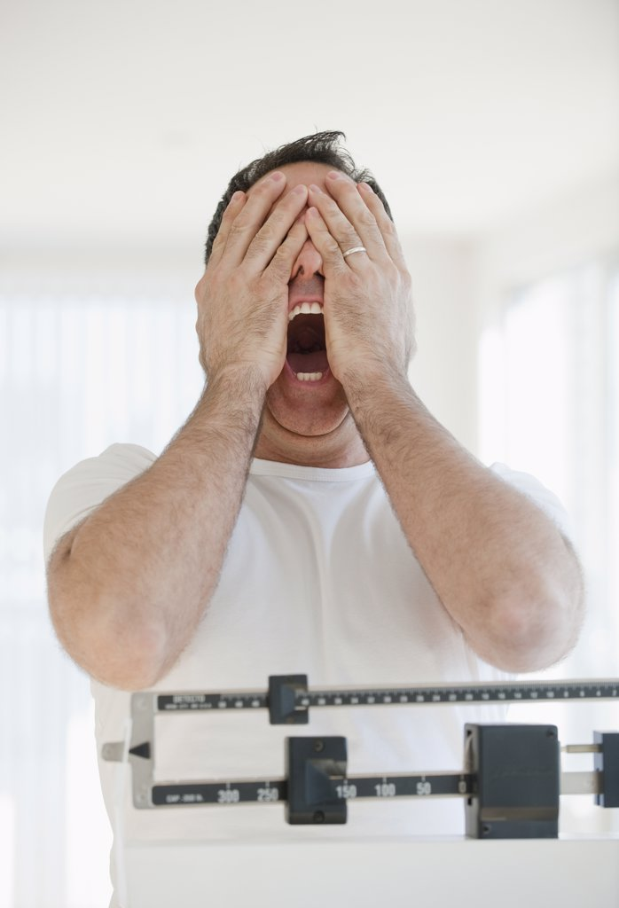 Mature man on scales screaming and covering his eyes : Stock Photo