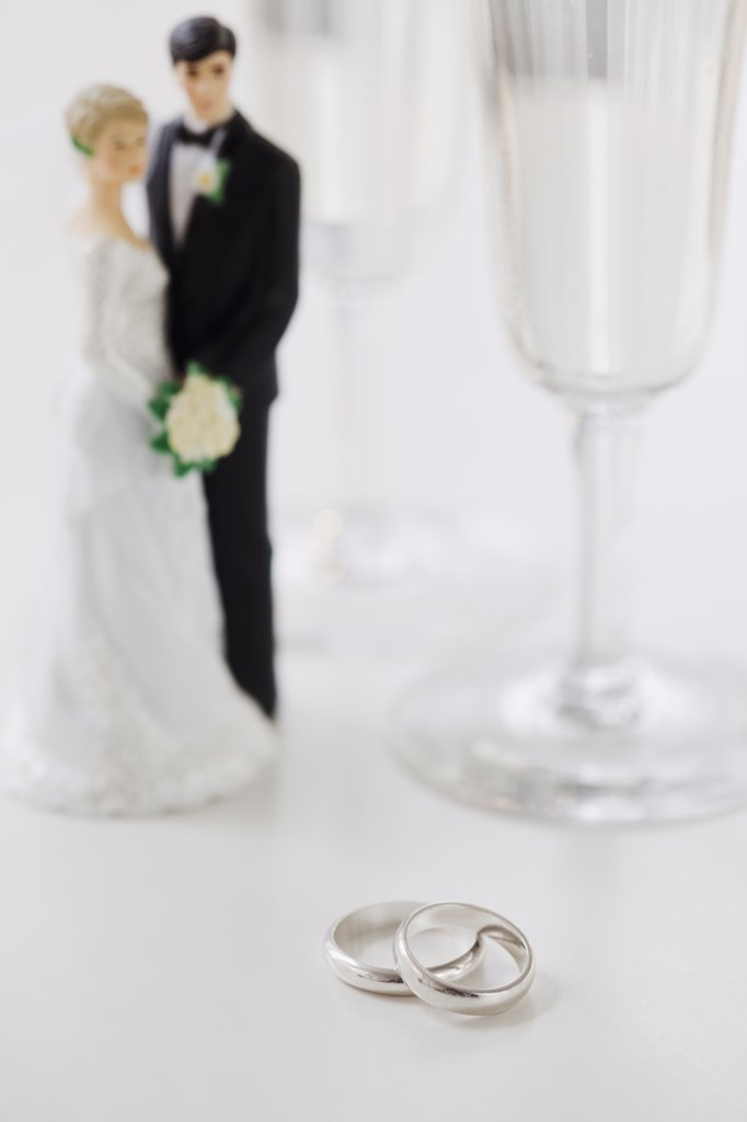 Stock Photo: 1795R-23050 Wedding rings by bride and groom cake toppers and wineglasses