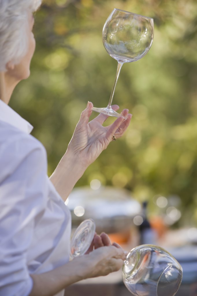 Stock Photo: 1795R-23209 Senior woman standing in garden and examining wineglasses