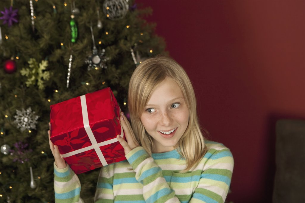 Teenage girl (10-12) shaking Christmas gift : Stock Photo