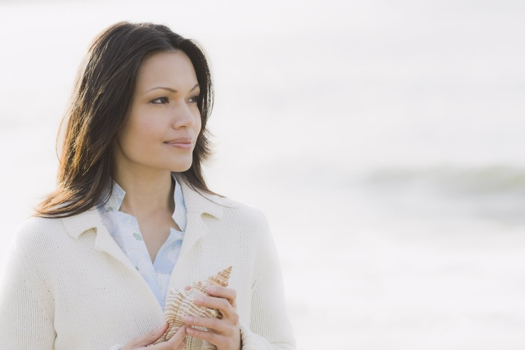 Stock Photo: 1795R-23317 Woman holding shell by sea