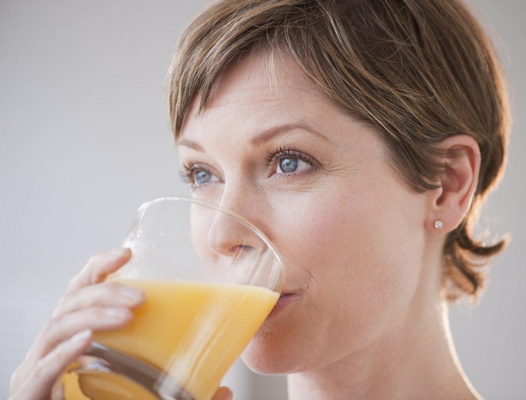 Stock Photo: 1795R-23552 Woman drinking orange juice