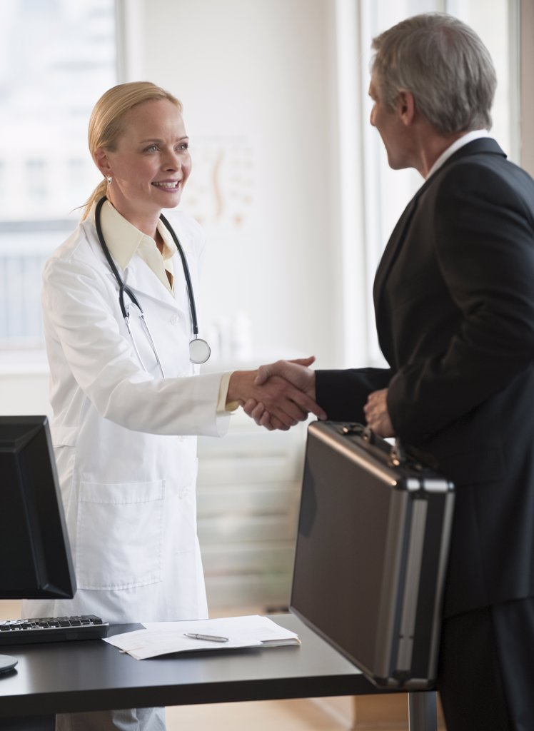 Female doctor greeting salesman : Stock Photo
