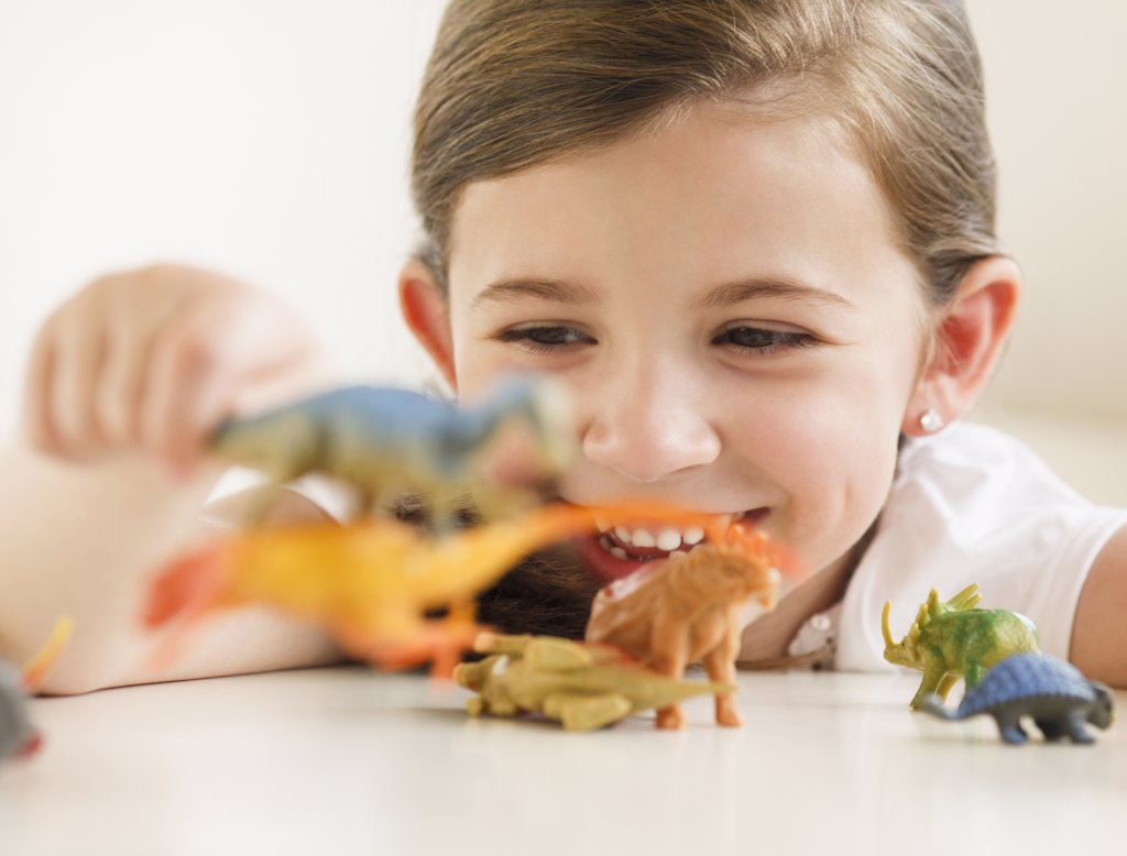 Child playing with dinosaurs : Stock Photo
