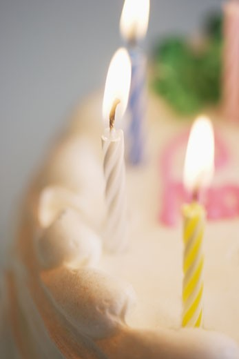 Lit candles on a birthday cake : Stock Photo