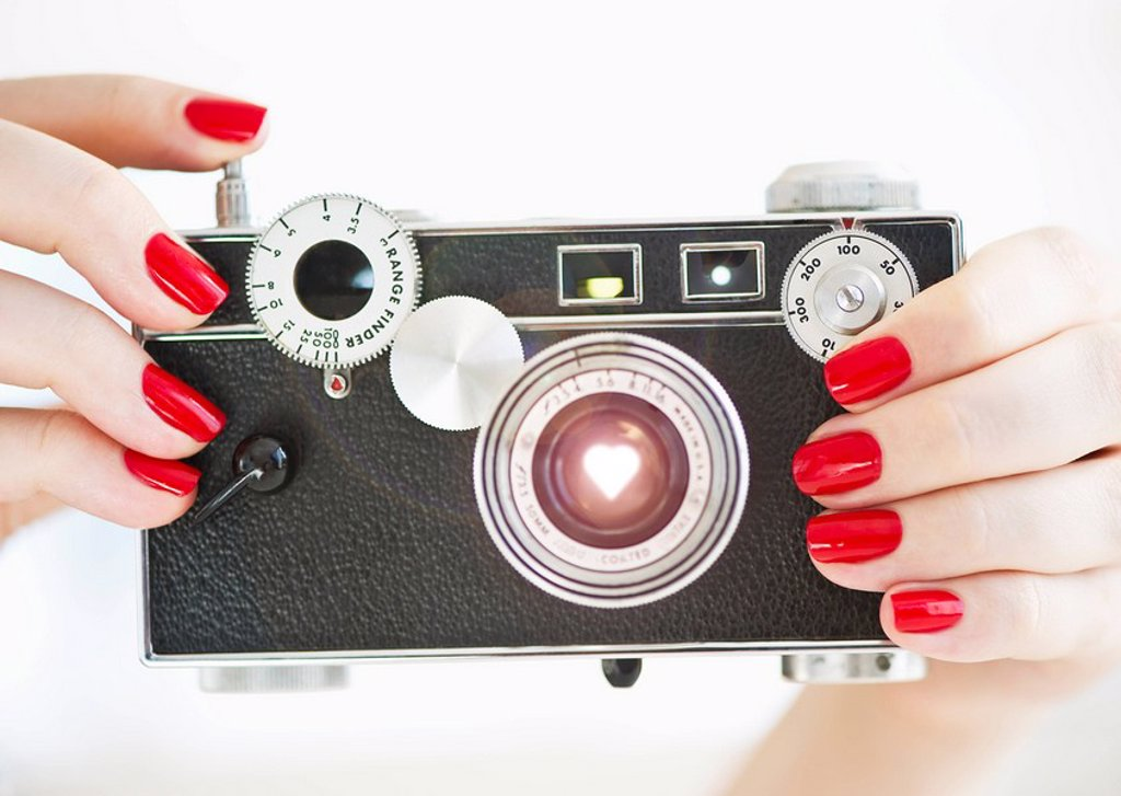 Antique camera being held by woman wearing red nail polish : Stock Photo