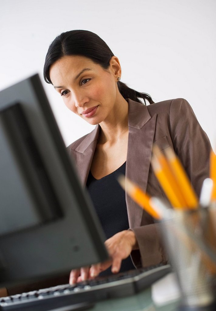 Pregnant businesswoman working on computer : Stock Photo