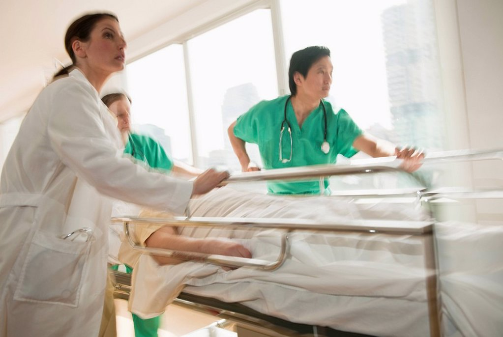 Healthcare workers pushing gurney in emergency room : Stock Photo