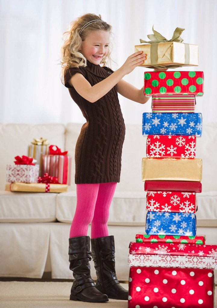 Young girl stacking Christmas gifts : Stock Photo