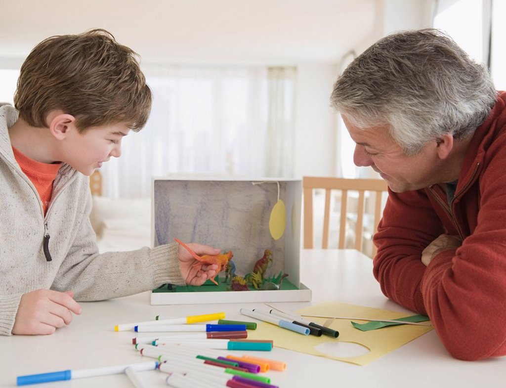 Stock Photo: 1795R-25496 Father and son working on dinosaur project