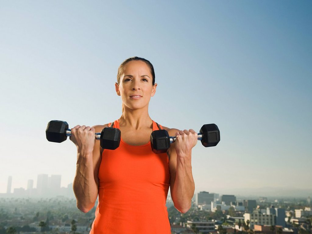 Stock Photo: 1795R-25885 Woman doing weight training
