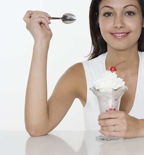Smiling woman with ice cream sundae : Stock Photo