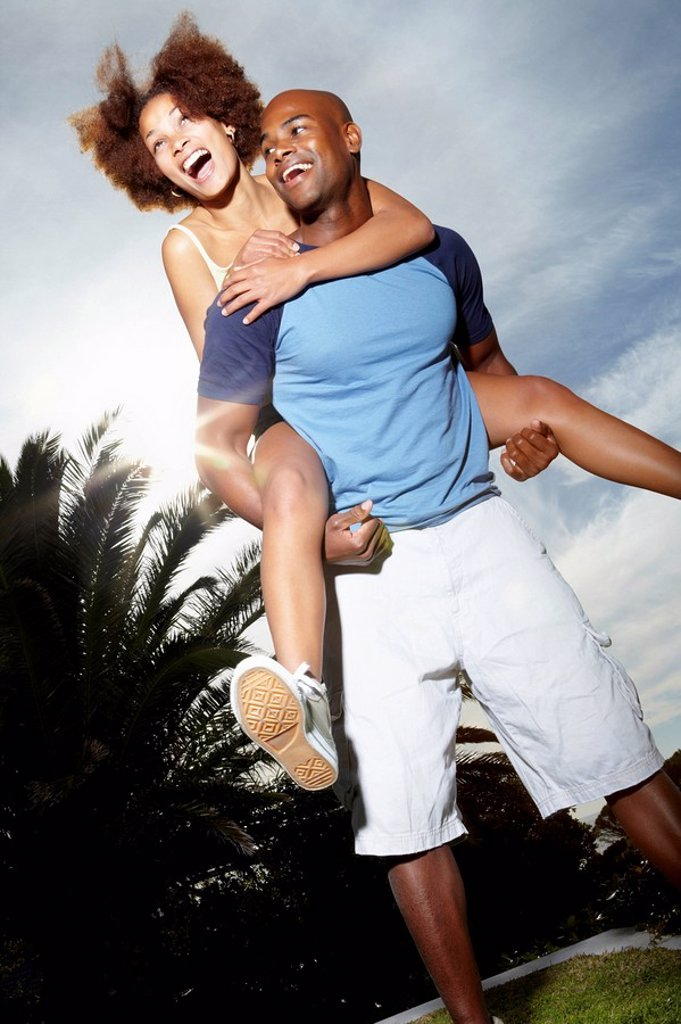 Man carrying woman on his back : Stock Photo