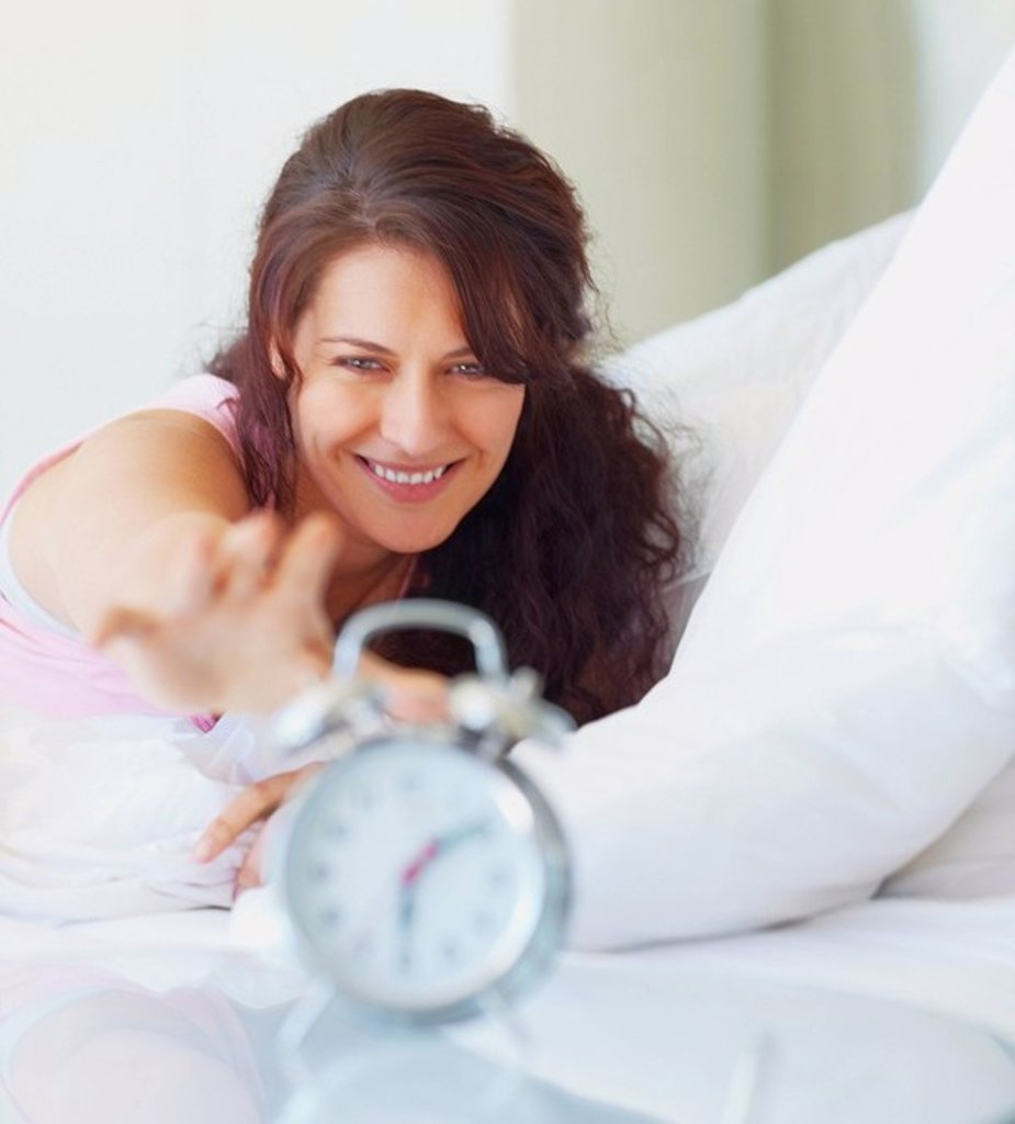 Woman reaching for alarm clock : Stock Photo