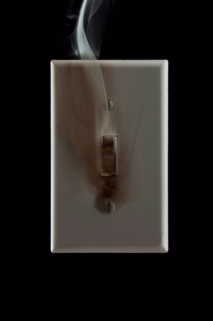 Smoke emanating from an electrical switch : Stock Photo