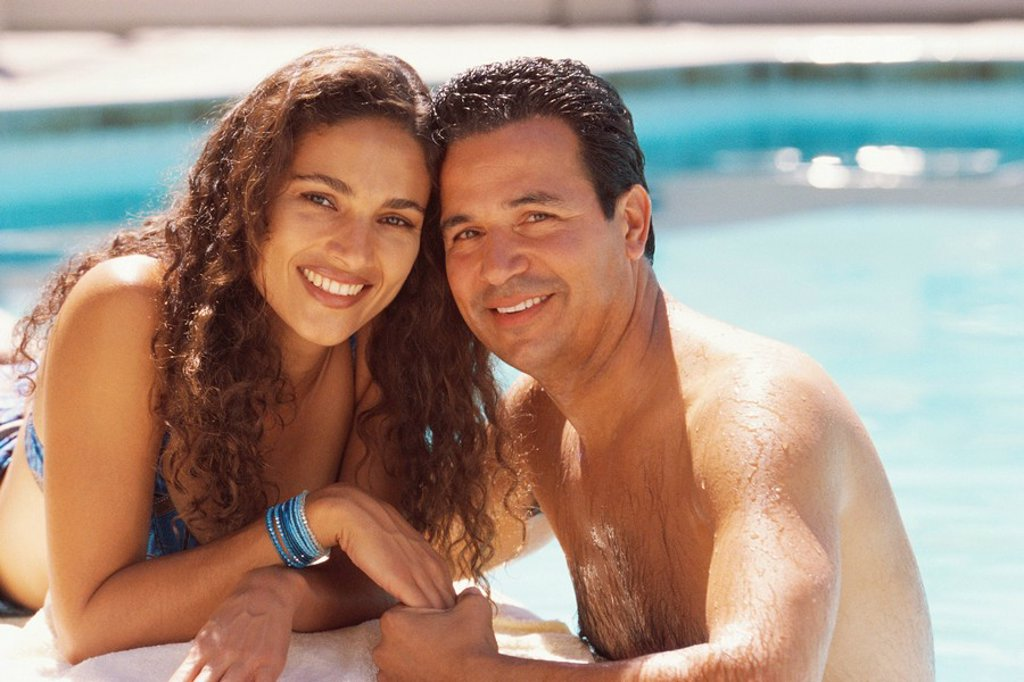 Couple relaxing by the pool : Stock Photo