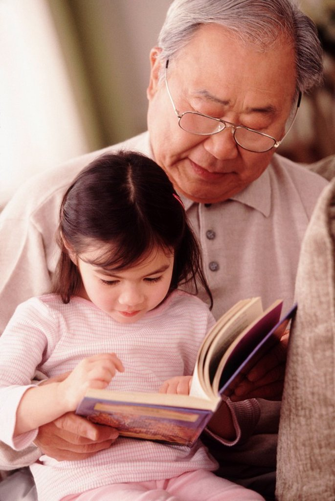 Grandfather reading to granddaughter : Stock Photo