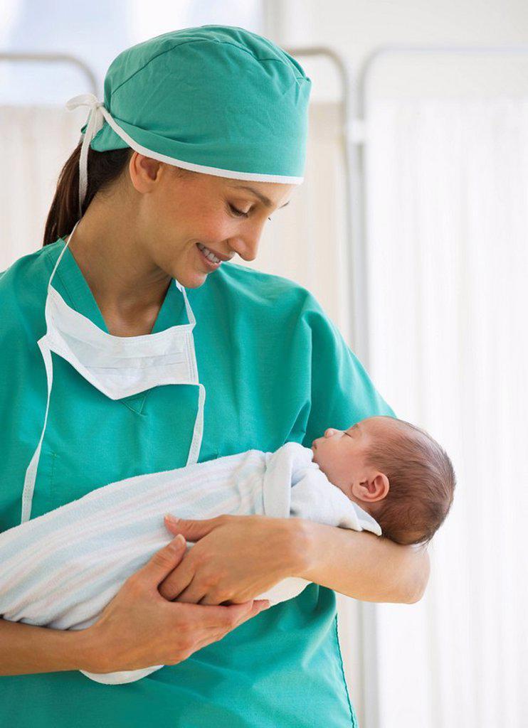 Stock Photo: 1795R-29002 Nurse holding swaddled baby