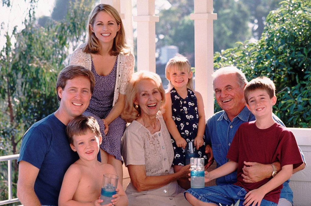 Three generations of family sitting on porch together : Stock Photo