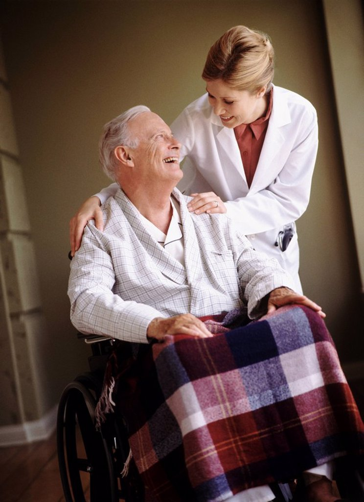 Doctor talking to senior man in wheelchair : Stock Photo