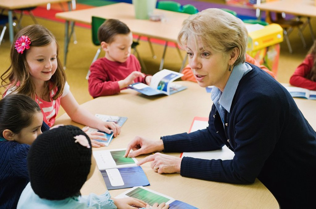 Kindergarten students sitting at table with teacher : Stock Photo