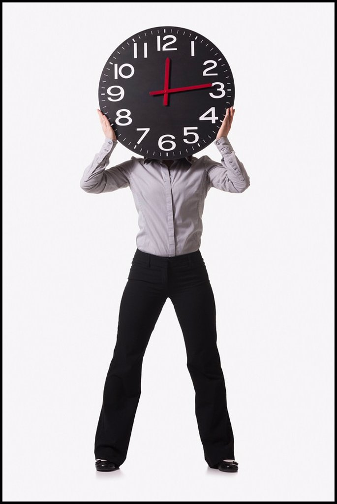 Businesswoman holding clock in front of her face : Stock Photo