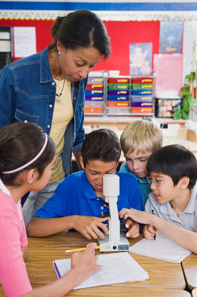 Teacher and elementary students looking at microscope : Stock Photo