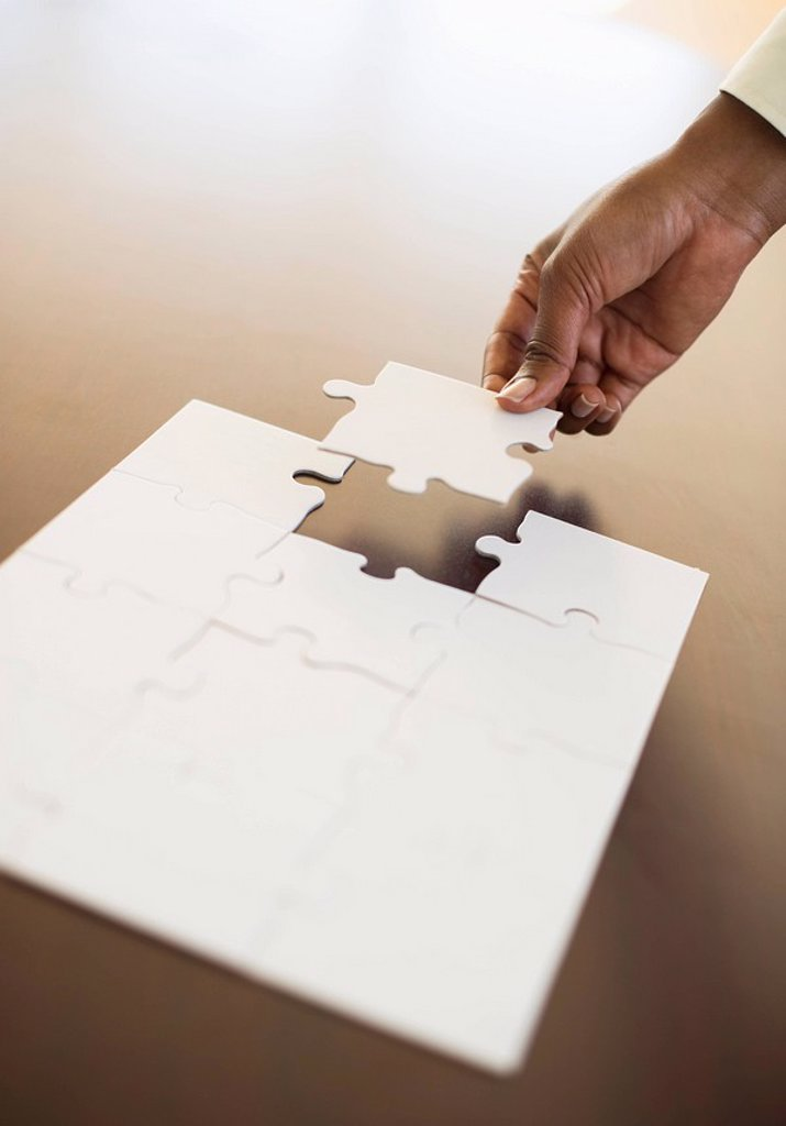 Stock Photo: 1795R-30116 Hand putting last puzzle piece in puzzle