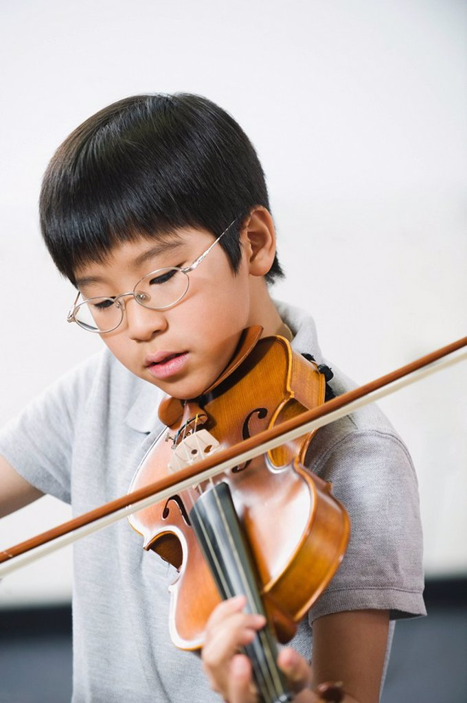 Elementary school student playing violin in music class : Stock Photo