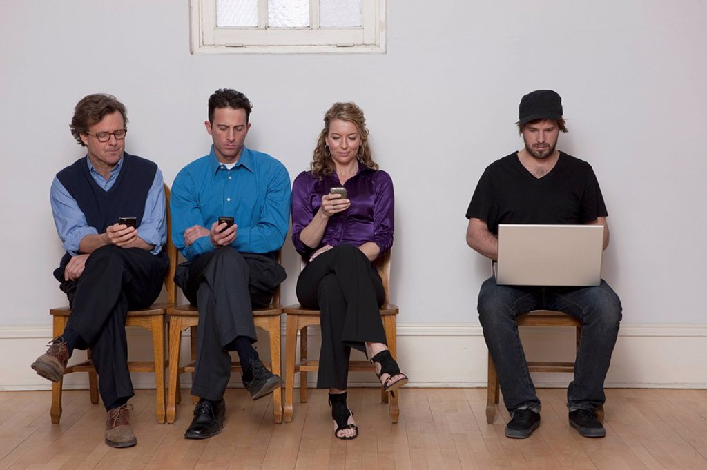 Four people sitting in a row : Stock Photo