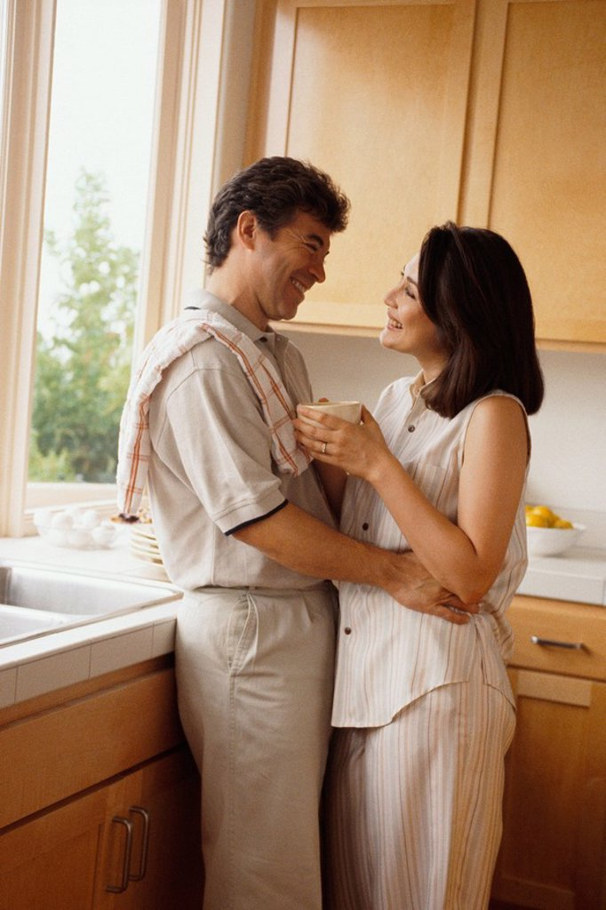 Couple embracing in the kitchen : Stock Photo