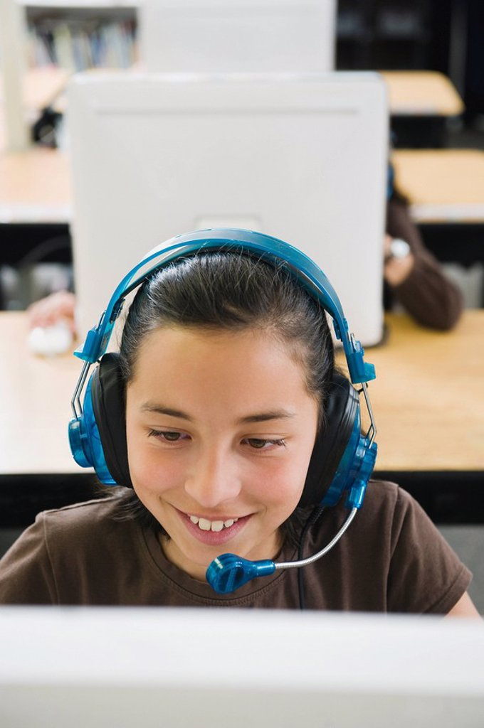 Elementary student wearing headphones in classroom : Stock Photo