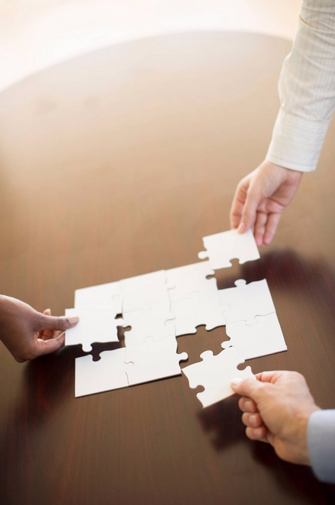 Stock Photo: 1795R-30854 Hands putting puzzle together