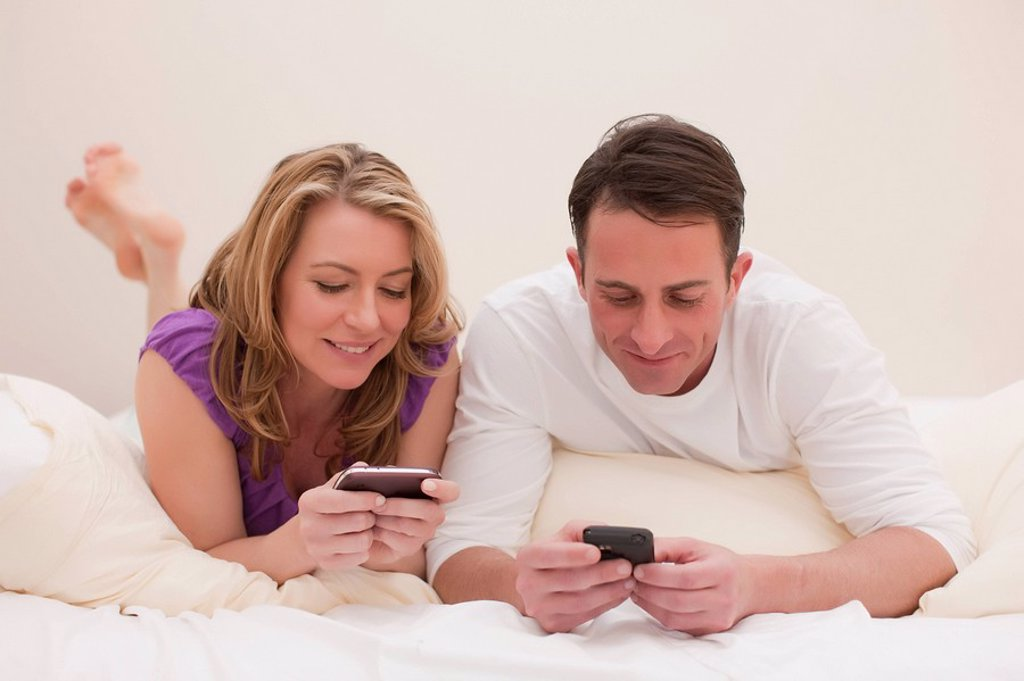 Couple lying on bed while texting : Stock Photo