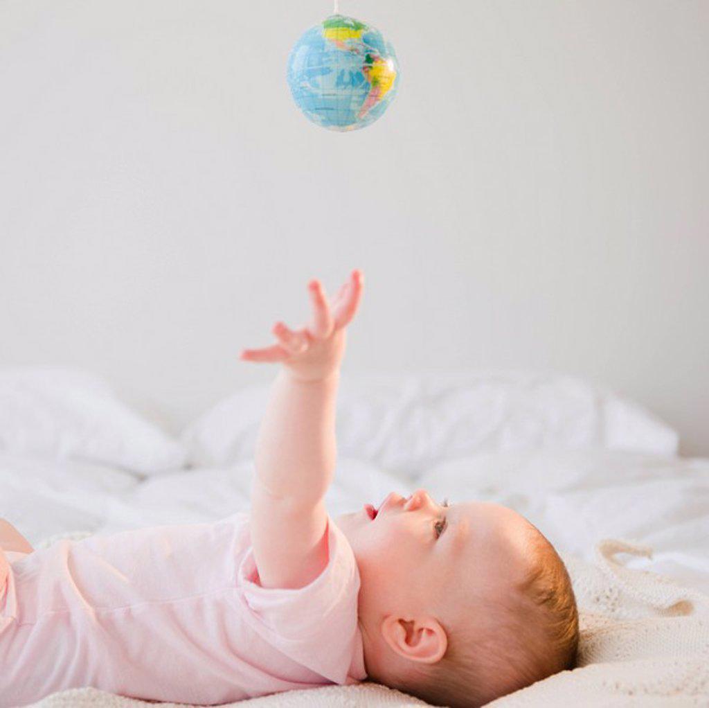 Baby reaching for globe : Stock Photo