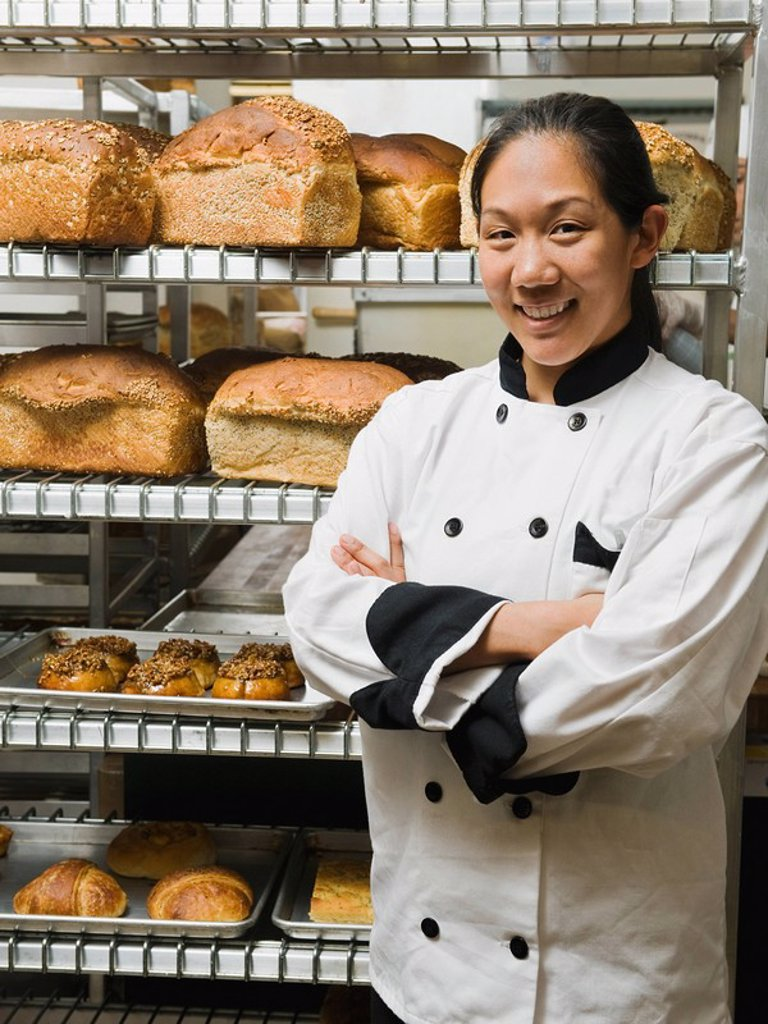 Chef standing beside trays of freshly baked goods : Stock Photo