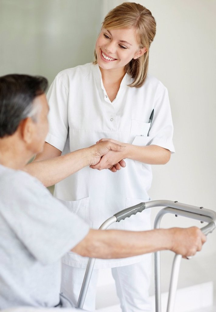 Nurse assisting patient with a walker : Stock Photo