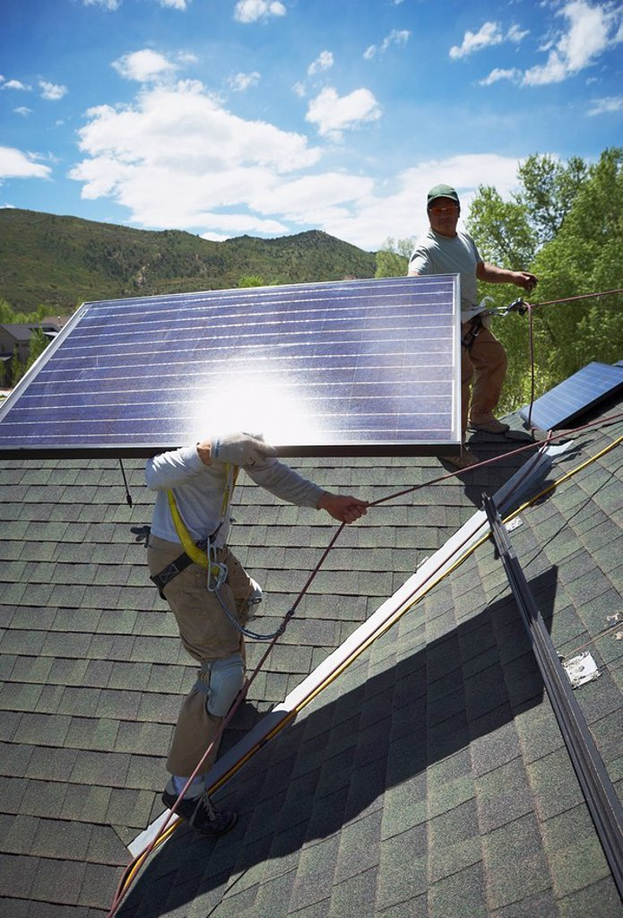 Stock Photo: 1795R-31572 Construction workers installing solar panels on roof